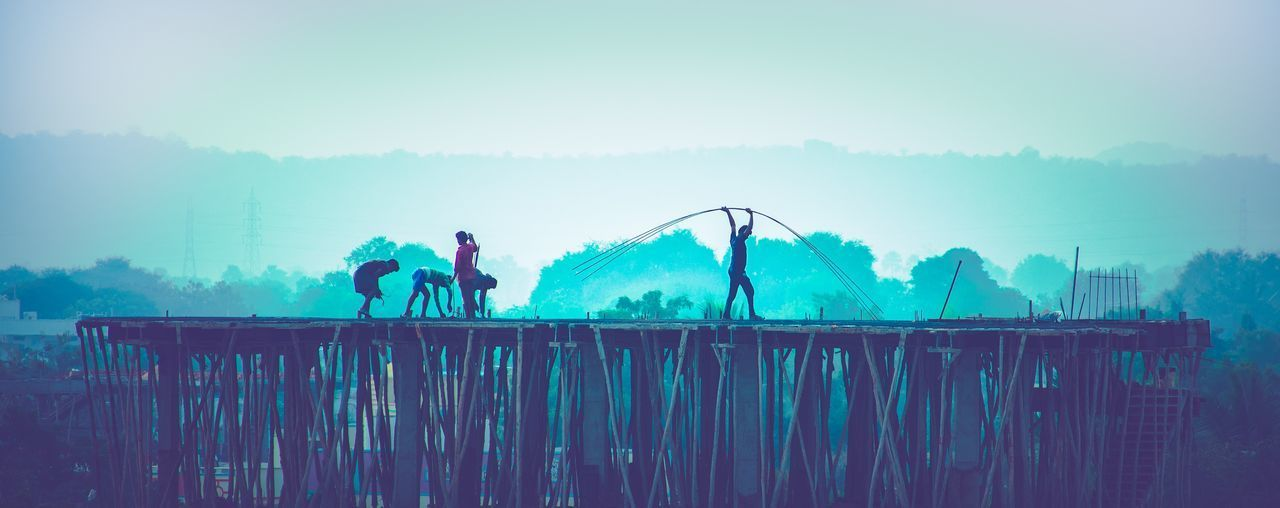 People working on land against sky