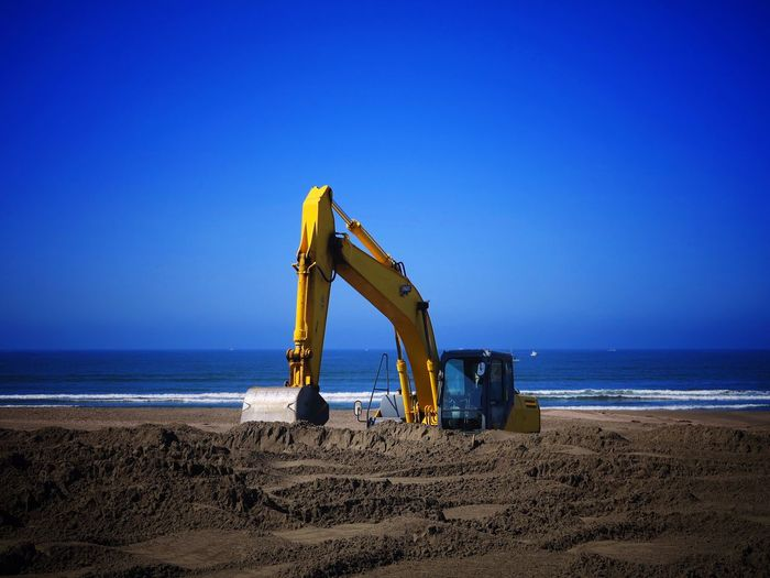 Crane At Digging Sand At Beach Against Clear Blue Sky