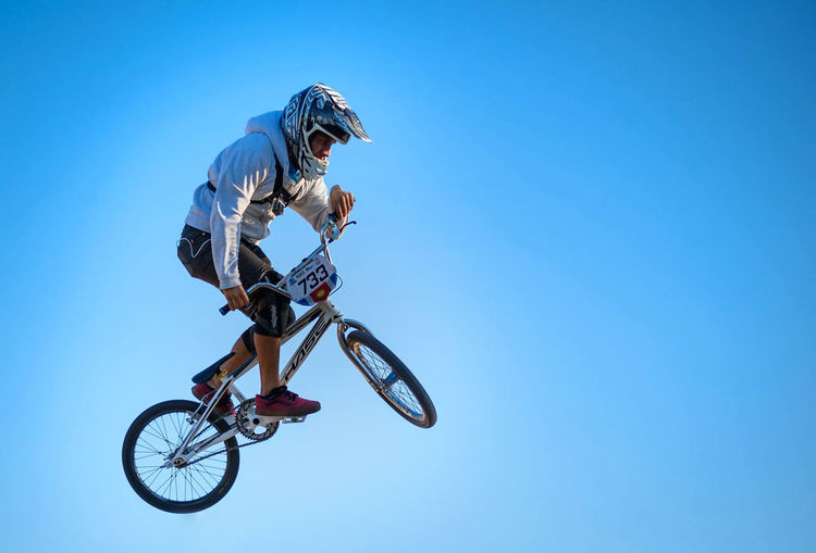 Full length of man in mid-air performing stunt on bicycle against clear blue sky