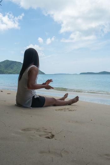Woman sitting on beach against sky