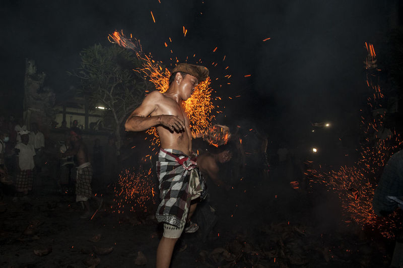 Shirtless Man Performing Stunt With Fire At Night