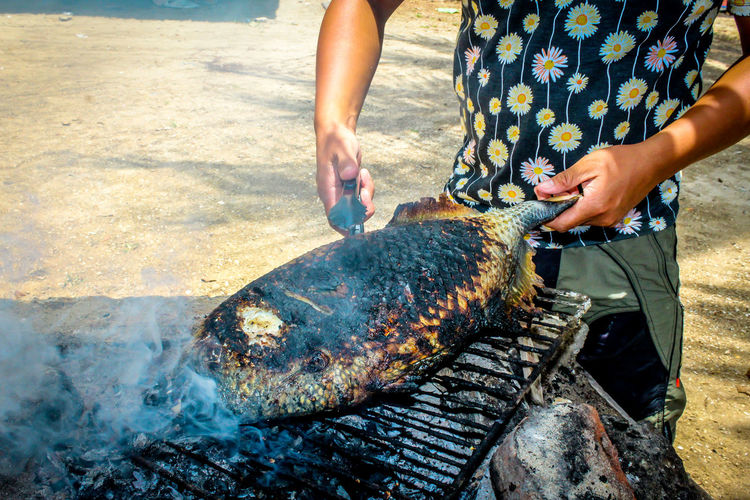 Midsection of man cooking fish on barbeque