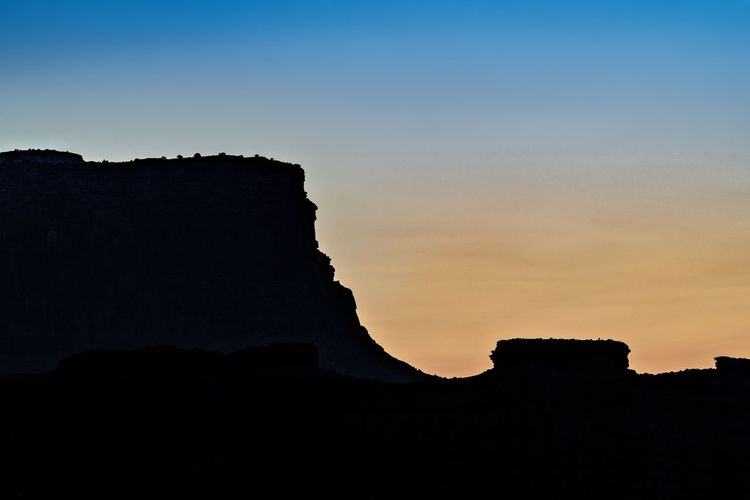 Low angle view of silhouette rock formation against sky at sunset