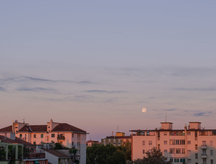 Full moon set over the city in the early morning after sunrise. Building Exterior Built Structure Architecture Building City Sky Cloud - Sky No People Nature Sunset Outdoors Dusk Town Copy Space City Life High Angle View Travel Destinations Moon Full Moon Moon Set Moon Rise Sunrise Moonset At Sunrise Pastel Colors Natural Light