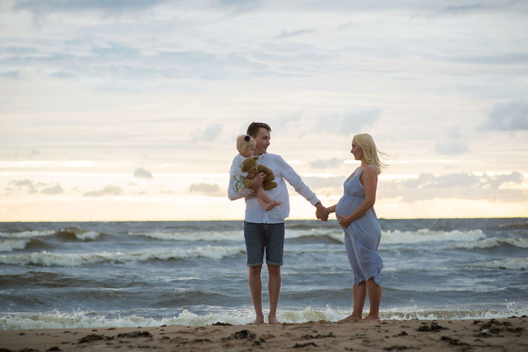Man with daughter holding pregnant woman hand at beach