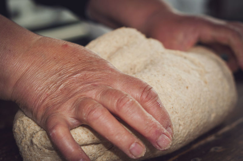 Cropped hands of woman kneading dough in kitchen