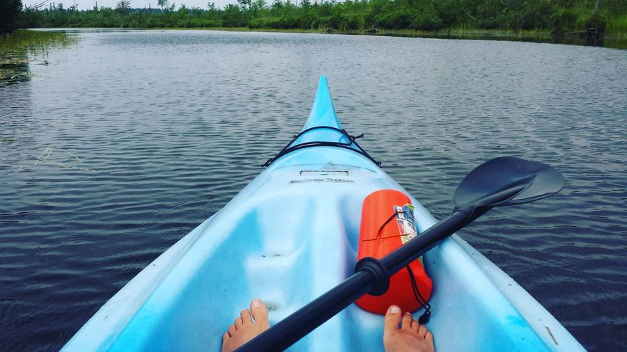 Cropped Image Of Man Relaxing On Blue Kayak In River