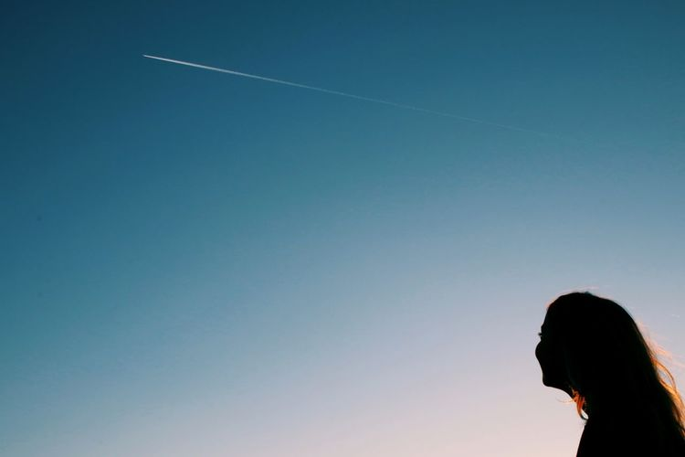 Silhouette Woman Looking At Vapor Trail Against Clear Blue Sky