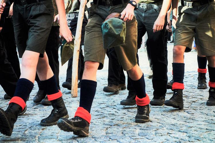 Low section of people in uniform walking on street