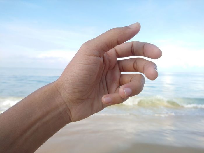 Palm finger and sea Human Hand Sea Beach Human Finger Hand Personal Perspective Fingernail Sky Close-up Horizon Over Water Wave Sandy Beach Crashing Surfboard Water Sport
