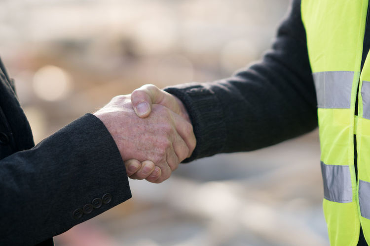 Cropped image of people shaking hands in city