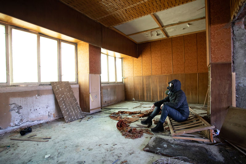 Side view of man sitting on chair in abandoned building