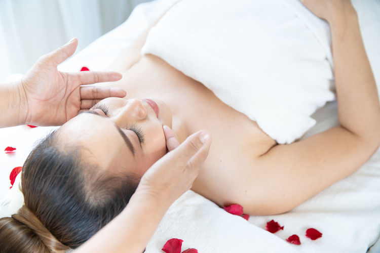 Cropped hands of therapist massaging woman at spa