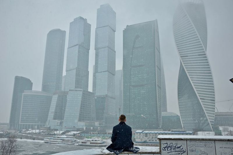 Rear view of man sitting against skyscrapers during snowfall