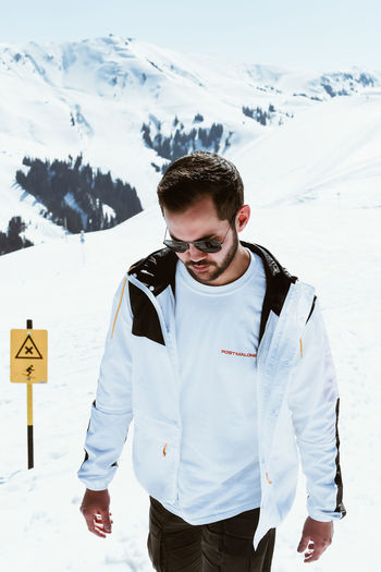 Snow One Person Leisure Activity Real People Winter Young Men Lifestyles Mountain Cold Temperature Young Adult Standing Day Nature Snow White Color Warm Clothing Boy Males  North Face Kitzbühel Cold Blue Sky White White Background Snowcapped Mountain
