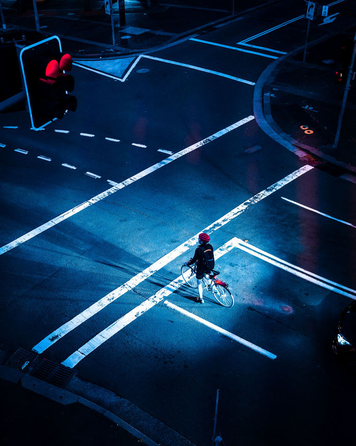 HIGH ANGLE VIEW OF MAN BICYCLING ON ROAD