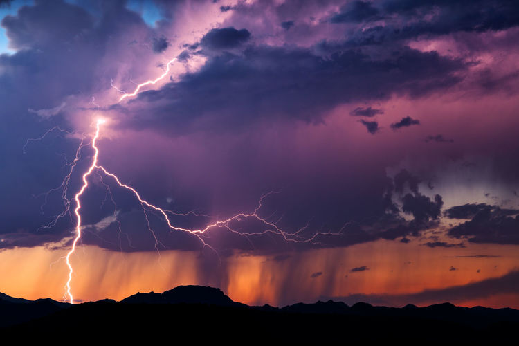 Lightning illuminates an isolated thunderstorm at sunset in the Arizona desert. Arizona Desert Awe Beauty In Nature Cloud - Sky Danger Dramatic Sky Forked Lightning Landscape Lightning Majestic Mountain Nature Night Outdoors Power In Nature Scenics Silhouette Sky Storm Storm Cloud Sunset Surreal Thunderstorm Weather