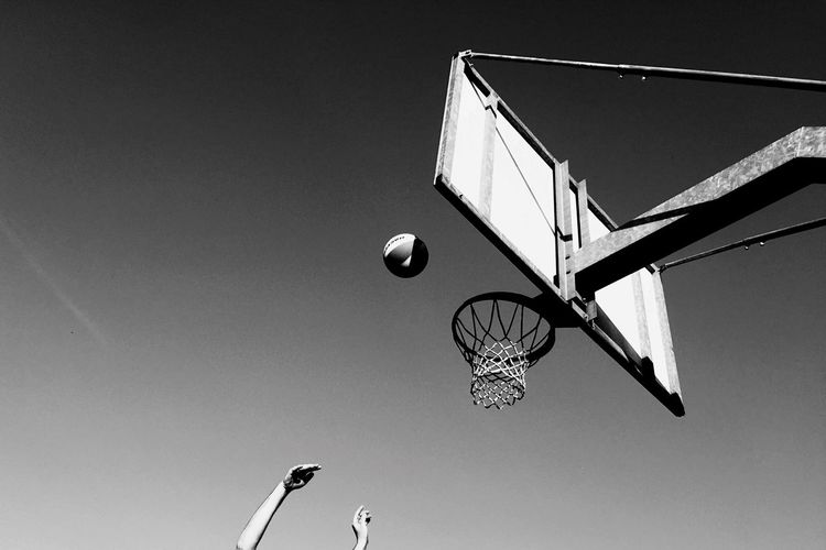 Low angle view of cropped hands playing basketball against clear sky