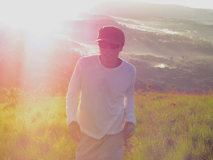 Man standing on landscape against sky during sunset