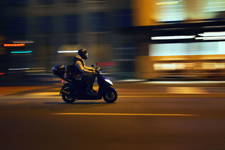 Man riding motorcycle on street at night