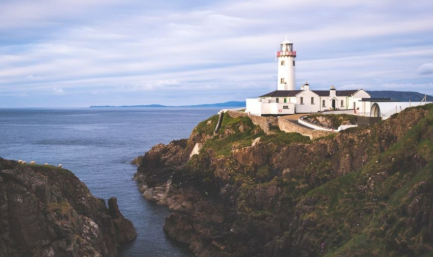 Fanad Head Lighthouse at sunset, Ireland. Cliffs Cloud Fanad Head Ireland Lighthouse Rock Architecture Beauty In Nature Building Exterior Built Structure Cloud - Sky Clouds Cove Golden Hour Lighthouse Nature No People Ocean Outdoors Rocks Sea Sky Sunset Tower Water