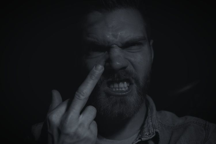 Close-up portrait of frustrated bearded man showing middle finger against black background