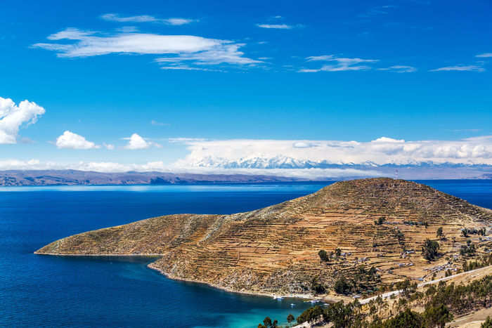 Terraced landscape of Isla del Sol with Andes mountains in the background on the Bolivian side of Lake Titicaca America Andean Blue Bolivia Coast Day High Isla Isladelsol Island Lake Landscape Latin Nature Outdoor Peru Rural Sea Sky Sol South Titicaca Titicaca Lake Travel Water