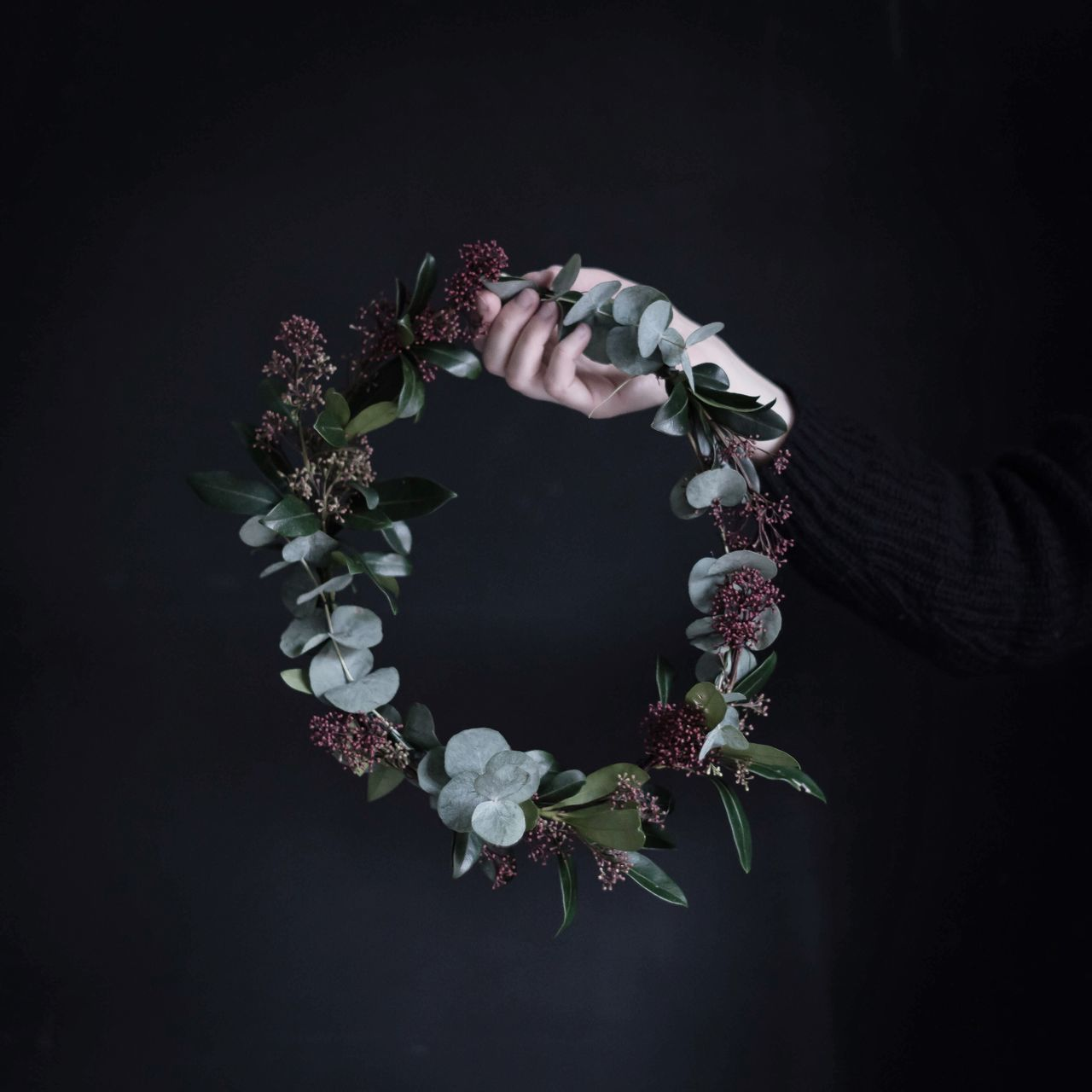 Woman holding flowers against black background