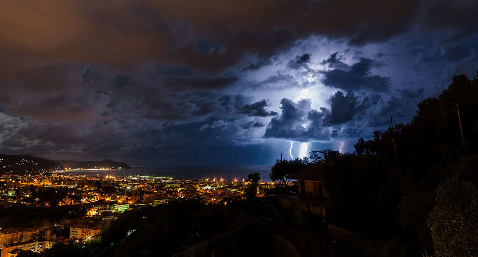Lightning storm over sea by townscape at night at chiavari