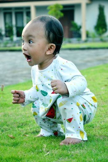 Cute baby girl shouting while crouching on grassy field
