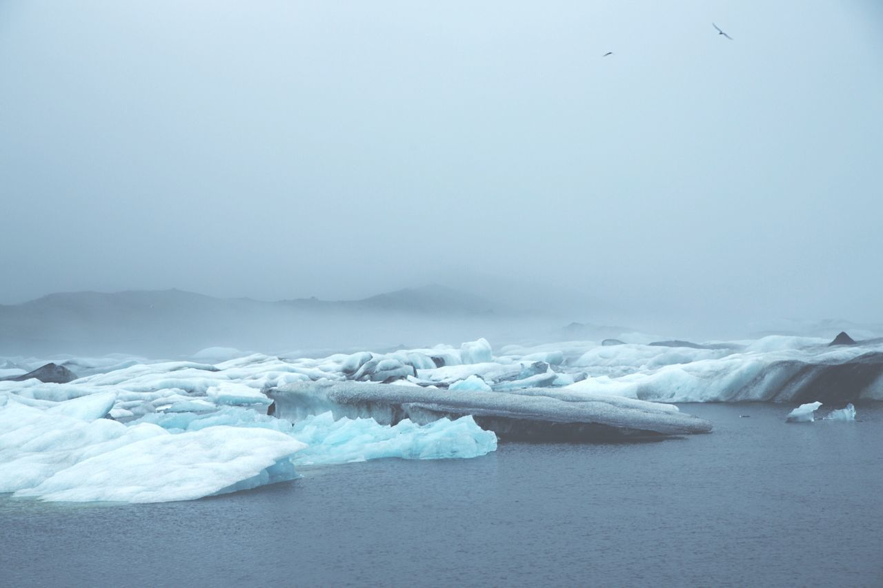 Idyllic shot of glaciers in lagoon under foggy weather