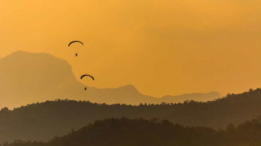 Paragliders flying over mountain range during sunset