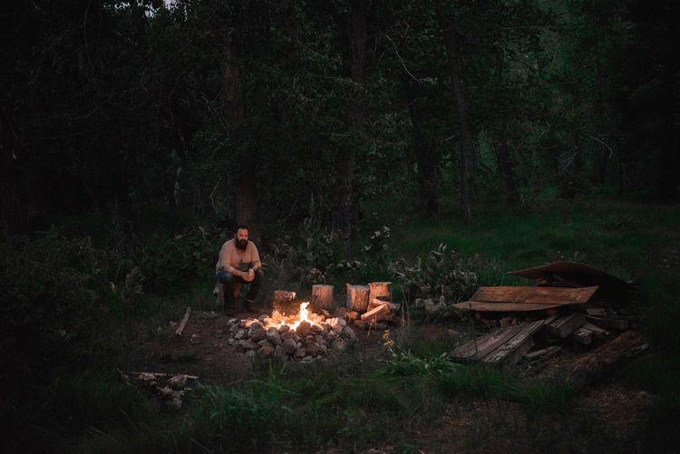 Portrait of mid adult man sitting by campfire in forest