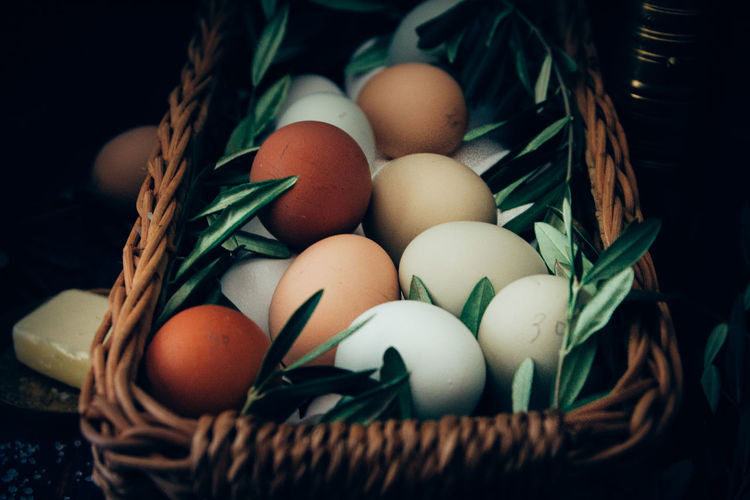 Close-Up Of Eggs And Herbs In Basket On Table