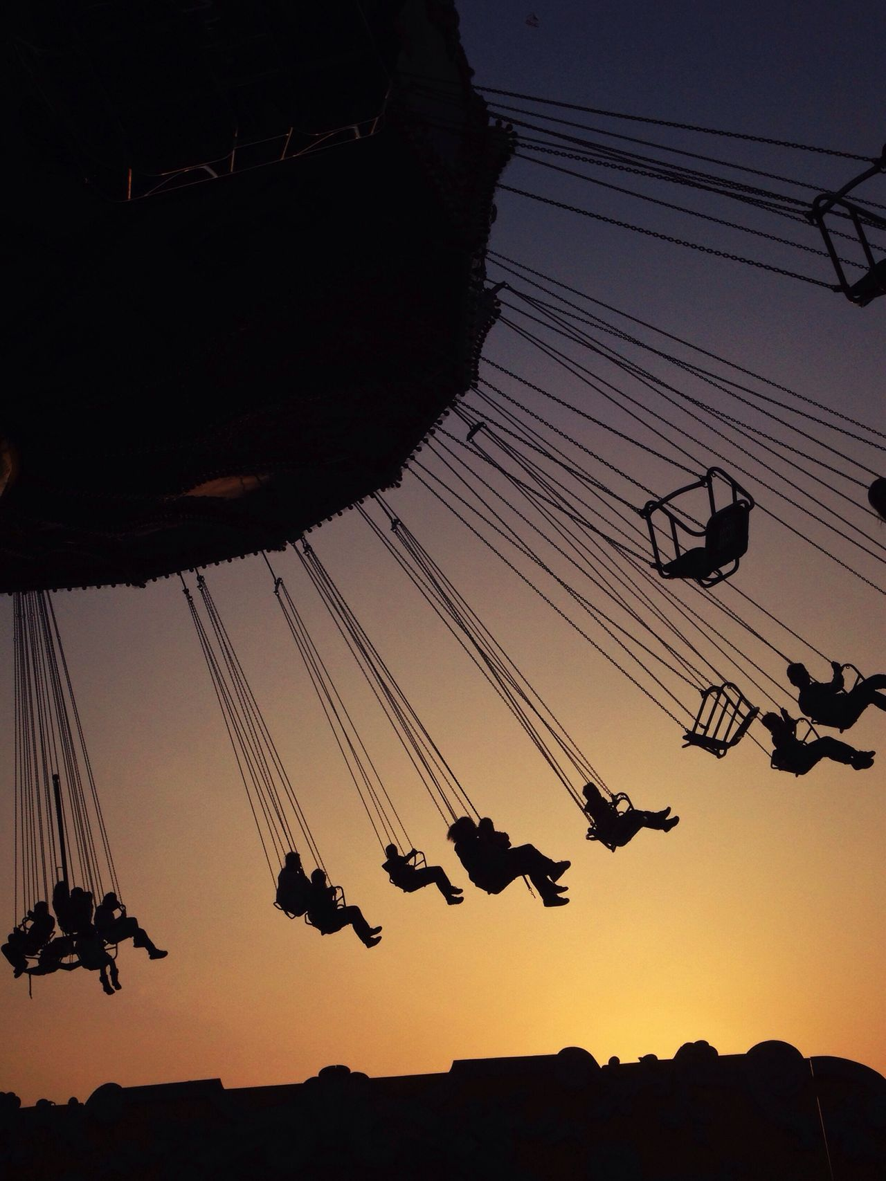 Low angle view of silhouette swing ride against clear sky