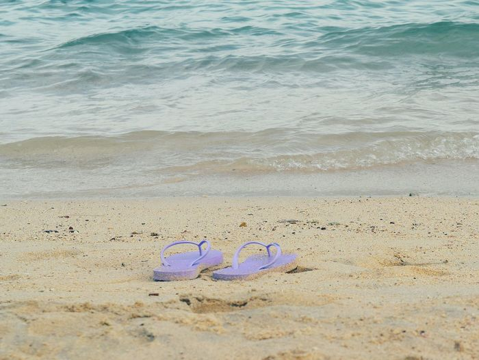 Women shoes on sand beach Sand Beach Shore Day Sea Nature Water Vacations Outdoors Beauty In Nature Foam Travel Summer Wave Blue Colorful Shoes ♥ Water Sea Copy Space