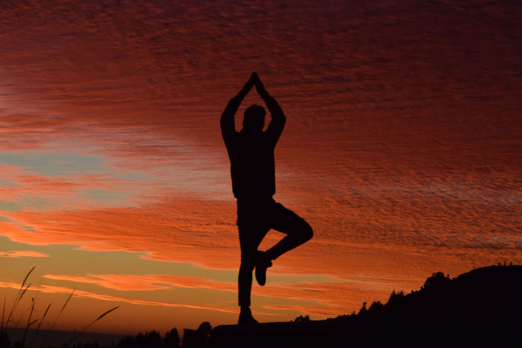 Silhouette man with arms raised standing against orange cloudy sky during sunset