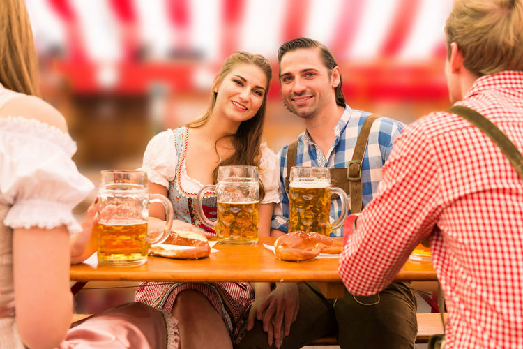 Portrait Man And Woman With Friends Having Beer At Table