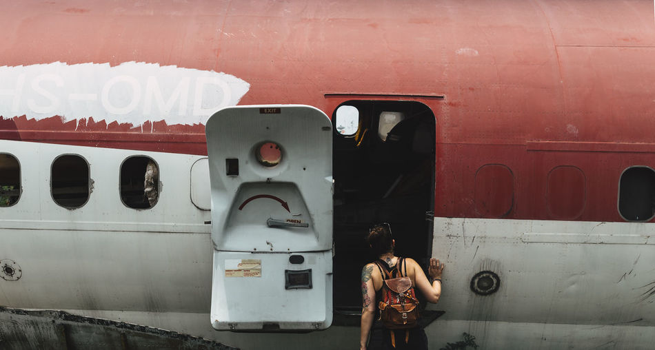 Rear View Of Woman Standing By Abandoned Airplane