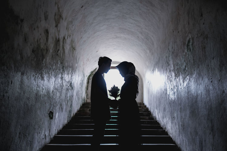 Side view of silhouette couple holding bouquet while standing on staircase