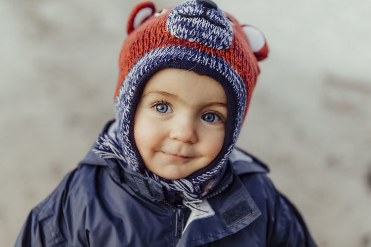 Portrait Of Cute Baby Girl Wearing Warm Clothing Outdoors