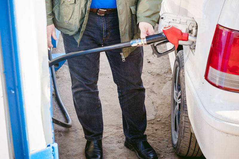 Low Section Of Man Filling Fuel In Car