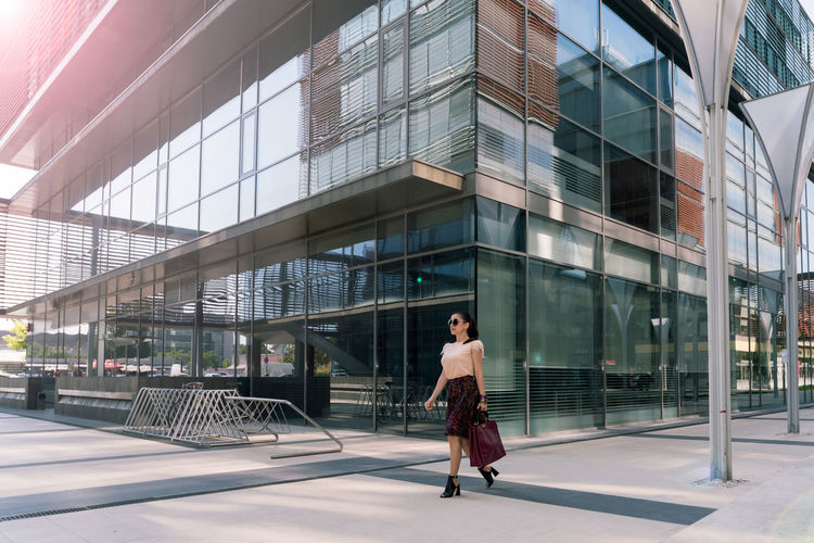 Full Length Of Woman Walking By Modern Building In City