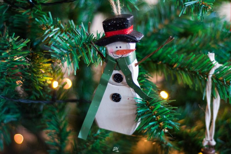 Close-Up Of Snowman Hanging On Illuminated Christmas Tree At Night