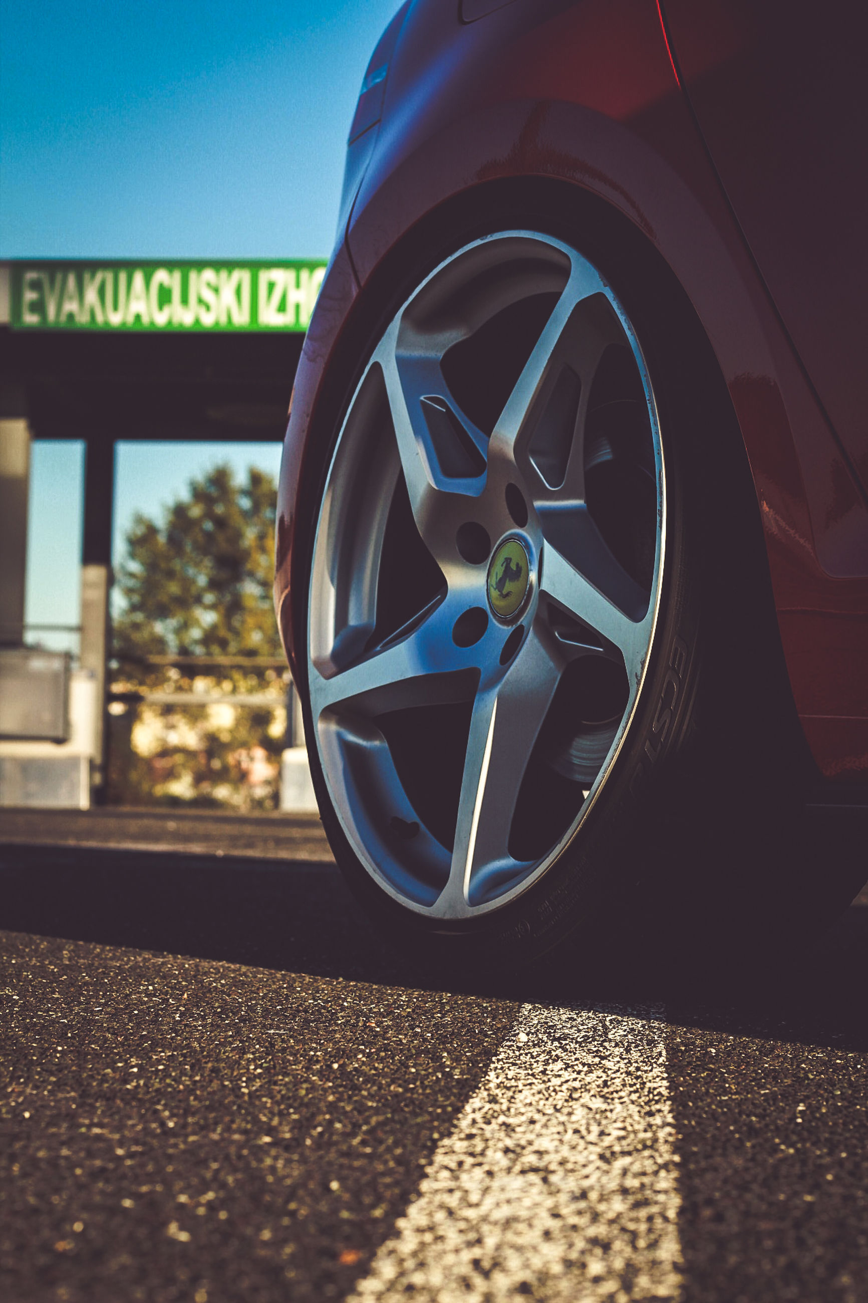 transportation, mode of transportation, road, car, sunlight, shadow, land vehicle, no people, motor vehicle, day, nature, reflection, wheel, close-up, outdoors, sign, city, shape, symbol, geometric shape, tire, silver colored