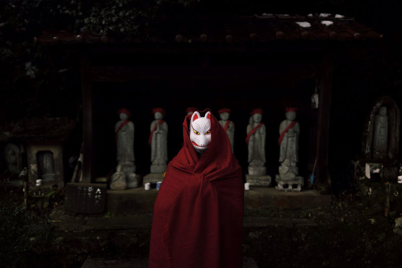 Person in fox mask standing in front of statues at night