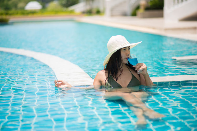 Adult Beautiful Woman Clothing Day Hat Holiday Leisure Activity Lifestyles Nature One Person Outdoors Pool Poolside Real People Relaxation Sun Hat Swimming Pool Water Women Young Women