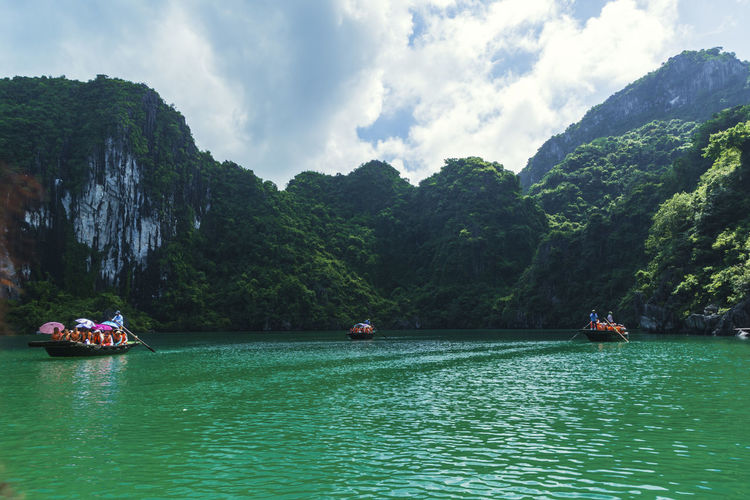 Beauty In Nature Cloud - Sky Day Large Group Of People Longtail Boat Men Mode Of Transport Mountain Mountain Range Nature Nautical Vessel Outdoors Rafting Real People River Rock - Object Scenics Sky Tranquil Scene Tranquility Transportation Tree Vietnam Halong Bay Water Waterfront Wooden Raft