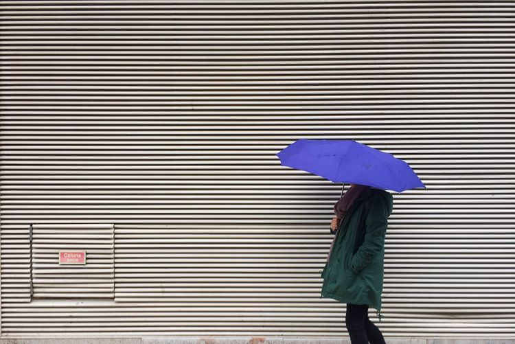 Side view of woman holding purple umbrella while walking by wall