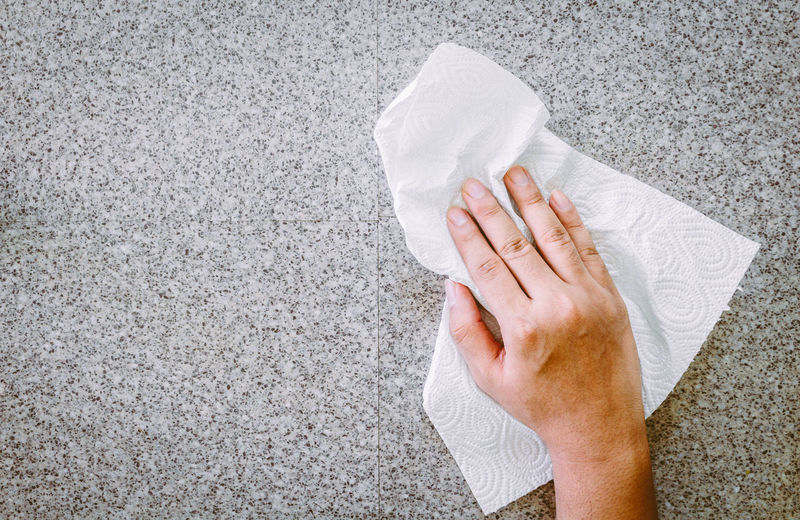 Cropped hand cleaning floor with tissue paper